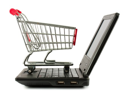 Shopping cart over a laptop keyboard isolated on white background photo