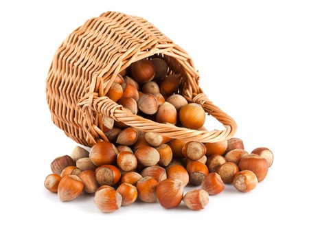 Wicker basket and hazelnuts isolated on a white background  photo
