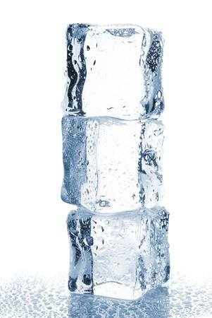 cubos de hielo: Tres cubos de hielo con gotas de agua aisladas sobre fondo blanco Foto de archivo