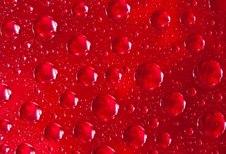 Abstract macro of water drops over red background photo