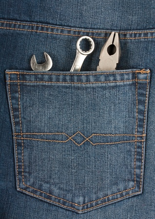 Pliers and wrenches in the pocket of blue jeans photo