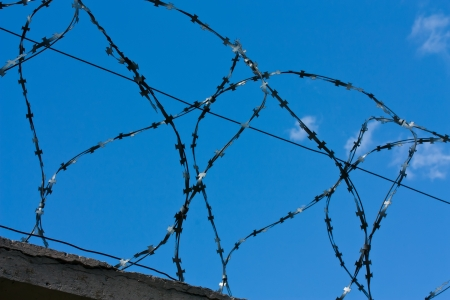 Barbed wire above the wall on blue sky background photo