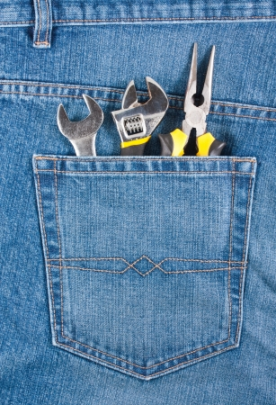 Several tools in a blue jeans pocket photo