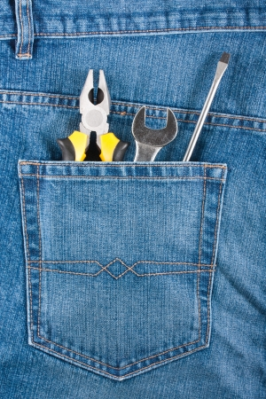 Screwdriver wrench and pliers on a blue jeans pocket photo