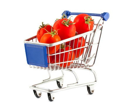 Ripe red tomatoes in shopping cart isolated on white background photo