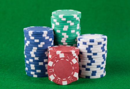 Poker chips on green playing table background photo
