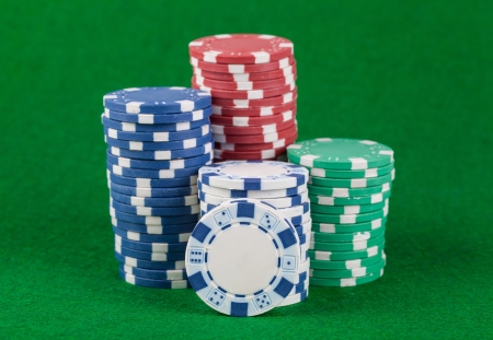Different casino chips on a green table background  photo
