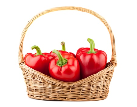 Sweet red pepper in wicker basket on white background photo