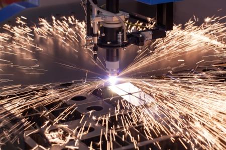 금속 플라즈마 절단 용 산업 기계. 그의 작품 불꽃 비행합니다.
