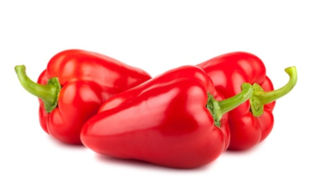 Three ripe red sweet peppers isolated on a white background