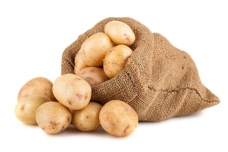 黄麻布の袋の白い背景で隔離の熟したジャガイモ