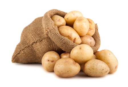 Ripe potatoes in burlap sack isolated on white background Imagens