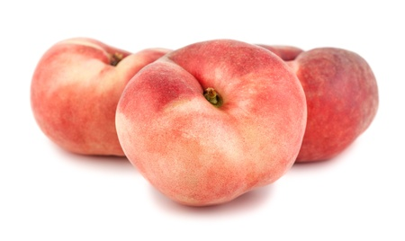 Three paraguayos flat peaches isolated on white background