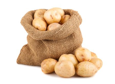 Ripe potatoes in burlap sack isolated on white background photo