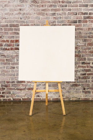 blank canvas: Easel with blank canvas on a brick wall background Stock Photo