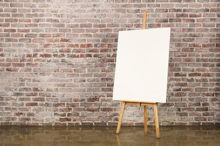 brick sign: Easel with blank canvas on a brick wall background Stock Photo