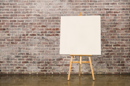 Easel with blank canvas on a brick wall background Stock Photo