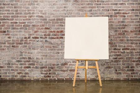 Schildersezel met leeg canvas op een bakstenen muur achtergrond