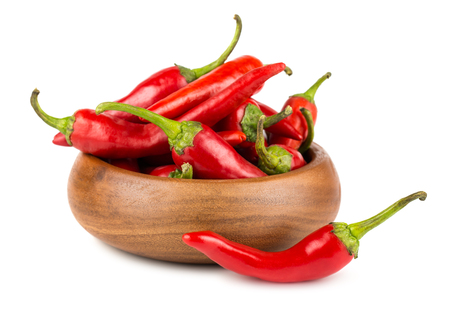 hot peppers: Red hot chili peppers in wooden bowl on white background