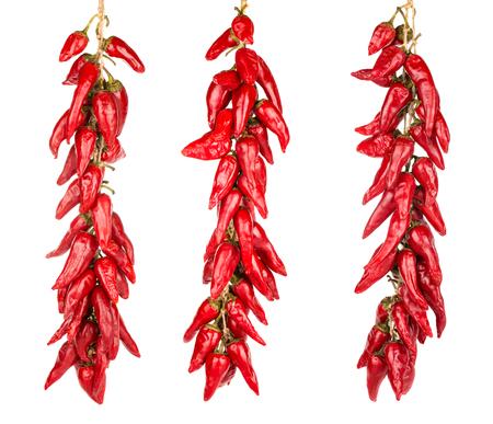 pimientos: Red hot chili peppers que cuelgan en una de tres cuerdas aislados en el fondo blanco