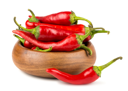 spicy chilli: Red hot chili peppers in wooden bowl on white background
