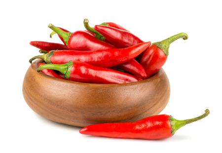 pimientos: Red hot chili peppers en cuenco de madera sobre fondo blanco