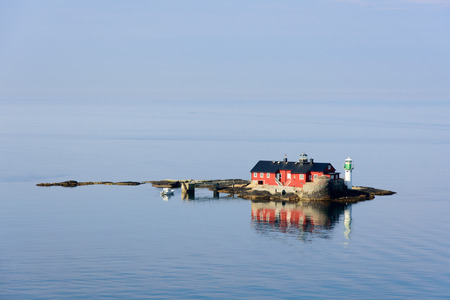 gothenburg: The old lighthouse of Botto. A red house on a very small rocky island serving as lighthouse. A remote island in a calm sea. Blue sky and morning sunlight. A small white motorboat mored at the island. Gothenburg, Sweden. Editorial