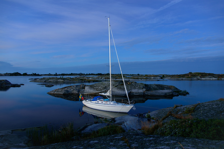 sailingboat: Blue midnight light over a mored sailingboat in the outer archipelago of Stockholm, Sweden