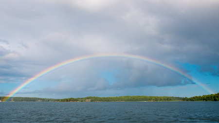 rainbow: A full rainbow arc over water and islands. Archipelago of Stockholm, Sweden. Stock Photo
