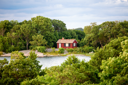 lonley: A lonley old red hut on an island in the archipelago. Embedded by green trees. Small bay in front of the house. Cloudy sky. Stockholm, Sweden.