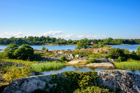 lonley: A lonley old red hut on an island in the archipelago. Embedded by green trees. Water and low skerries in front. Blue sky. Stockholm, Sweden.