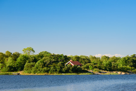 lonley: A lonley old red hut on an island in the archipelago. Embedded by green trees. Water in front. Blue sky. Stockholm, Sweden.