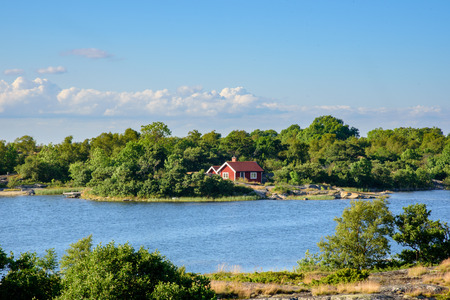 lonley: A lonley old red hut on an island in the archipelago. Embedded by green trees. Water in front f the house. Blue sky. Stockholm, Sweden. Stock Photo