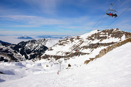 schweiz: Ski slopes in the french alps. Downhill view above the clouds. A chair lift is taking skiiers higher up out of the picture to the upper right.