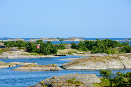 lonley: A lonley old red hut on a skerry in the archipelago. Embedded by green trees. Water and low skerries in front and behind. Blue sky. Stockholm, Sweden.