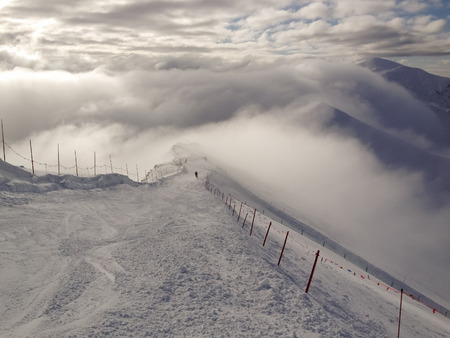 polen: Ski slope on a mountainridge where the clouds are passing by. Kasprowy Wierch in the Tatra mountains, Zakopane, Polen