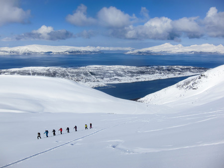ski walking: A group of people randonee ski walking high above the fjords. Lyngen Alps, Norway Stock Photo