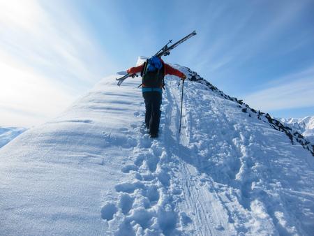 polar climate: One man walking in the snow on a mountain ridge towards the top. Lyngen Alps, Norway.