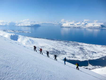 Ski Area: A group of people randonee ski walking high above the fjords. Lyngen Alps, Norway Stock Photo
