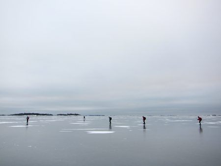 skating on thin ice: A group of people skating on newly frozen thin ice in the archipelago. Stockholm, Sweden. Stock Photo