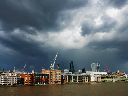 financial district: Dark clouds over Londons financial district. Buildings in sunshine.