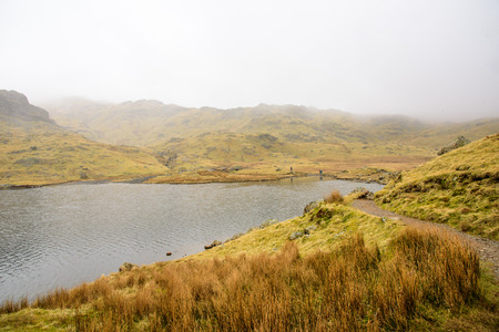 langdale: Trail around a small mountain lake. Green grass covered mountains and distant hikers. Lake District, England.