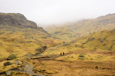 langdale: Mountain trail with two hikers. Lake District, England. Stock Photo