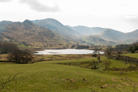 langdale: A small lake in the Lake District in England. Grass field in front. Mountains as background. Stock Photo
