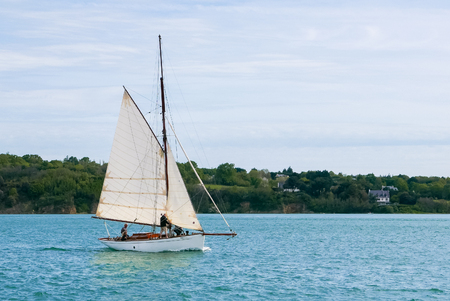 gaff: Small old gaff rig wooden sailboat. Sailing with a few people on board.