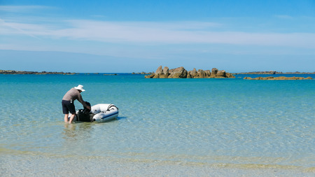 dingy: A man in sun hat is going with the dingy in shallow tropical colored water. Small rocky islands. Archipelago of Iles de Chausey, Brittany, France.