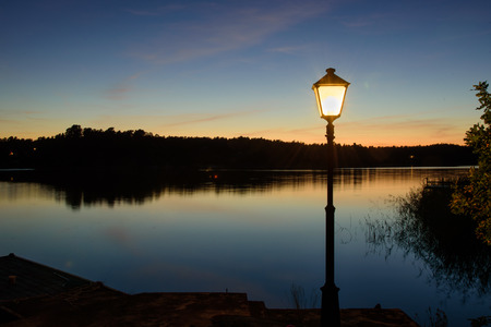 lamp post: Calm evening in Stockholm archipelago. Jetty with single lamp post.