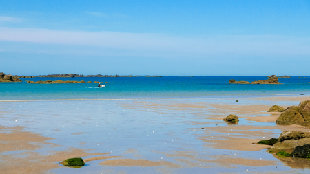 One man in a dingy taking off towards the horizon. Tropical colored water, Sandy beach and small rocky islands. Archipelago of Iles de Chausey, Brittany, France. Stock Photo