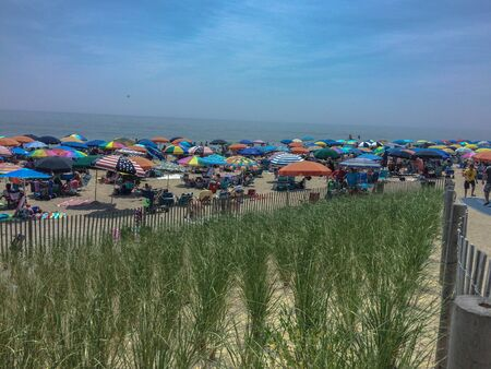 Bethany Beach, Delaware, Fourth of July crowds hide under umbrellas looking for shade along the sandy coast past the dunes. Stock Photo