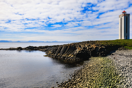 lighthouse and basalt columns at kalfshamarsvik on the coast of the ocean in iceland